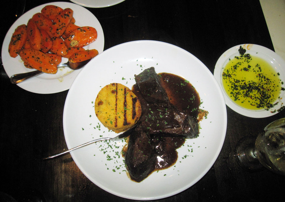 Photo - This May 28, 2014 photo shows braised short ribs, served with a crispy cake of polenta, and a side dish of carrots slice in long ovals, cooked in Marsala, at Antica, a restaurant in Chadds Ford, Pa. The restaurant is located near the Brandywine River Museum, which has an extensive collection of artwork by the Wyeth family and offers tours of nearby homes and studios where N.C. Wyeth, his son Andrew Wyeth and grandson Jamie Wyeth lived and worked. The restaurant is decorated with prints of Wyeth artwork. (AP Photo/Beth J. Harpaz)