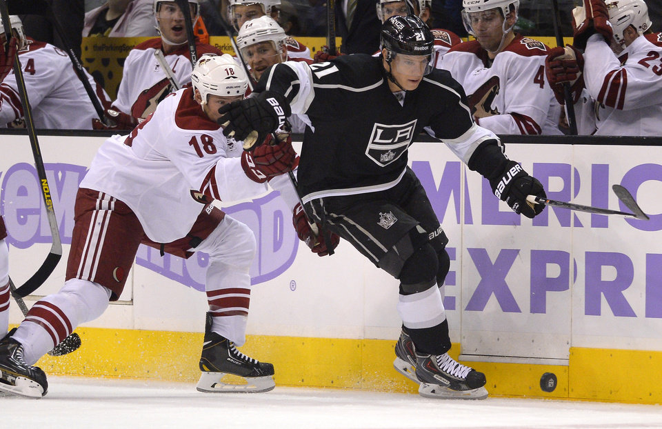 Photo - Los Angeles Kings right wing Matt Frattin, right, and Phoenix Coyotes left wing David Moss battle for the puck during the second period of their NHL hockey game, Thursday, Oct. 24, 2013, in Los Angeles. (AP Photo/Mark J. Terrill)
