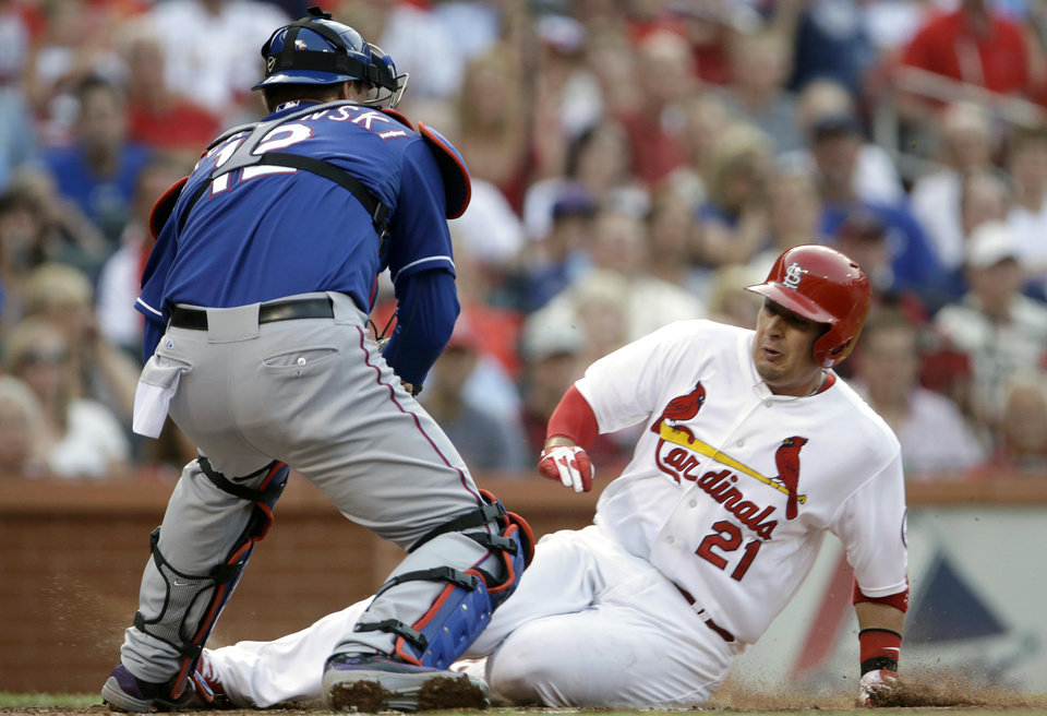 St. Louis Cardinals' Allen Craig, right, is tagged out at home by Texas Rangers catcher A.J. Pierzynski during the first inning of a baseball game on Friday, June 21, 2013, in St. Louis. (AP Photo/Jeff Roberson)