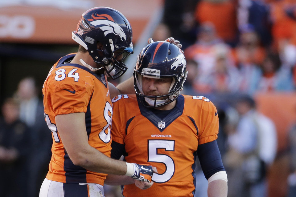 Photo - Denver Broncos tight end Jacob Tamme congratulates Denver Broncos kicker Matt Prater (5) on his field goal during the second half of the AFC Championship NFL playoff football game in Denver, Sunday, Jan. 19, 2014. (AP Photo/Charlie Riedel)
