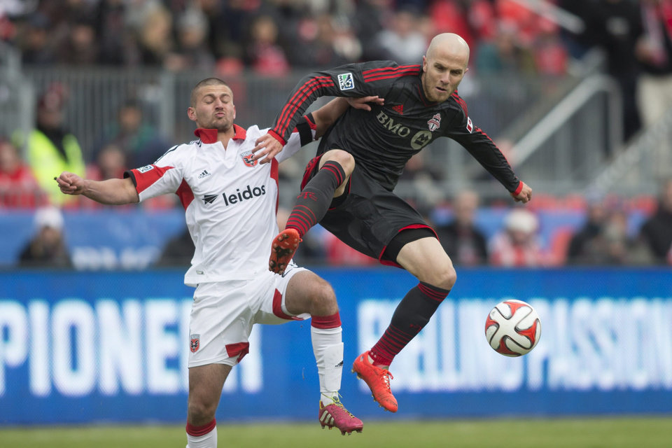 Photo - Toronto FC 's Michael Bradley, right, battles for the ball with D.C. United's Perry Kitchen during the first half of an MLS soccer game in Toronto on Saturday, March 22, 2014. (AP Photo/The Canadian Press, Chris Young)