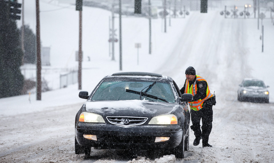 Photo - Greensboro police officer A.R. Schoonmaker pushes a car, which became stuck on a hill along the 600 block of West Market St. during the heavy snow in the downtown area on Wednesday, Feb. 12, 2014, in Greensboro, N.C. (AP Photo/News & Record, Jerry Wolford)