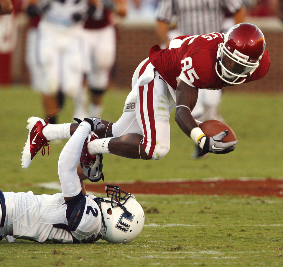 Photo - Ryan Broyles (85) is tackled by Cameron Sanders (2) after a long catch and run during the first half of the college football game between the University of Oklahoma Sooners (OU) and Utah State University Aggies (USU) at the Gaylord Family-Oklahoma Memorial Stadium on Saturday, Sept. 4, 2010, in Norman, Okla.   Photo by Steve Sisney, The Oklahoman