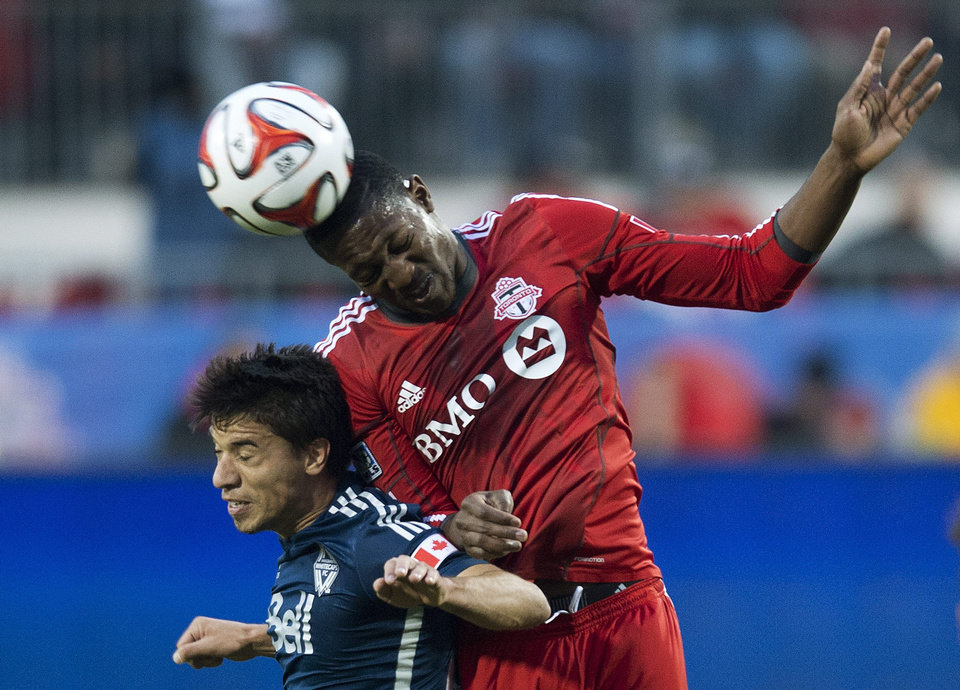 Photo - Toronto FC defender Doneil Henry, right, heads the ball against Vancouver Whitecaps forward Nicolas Mezquida, left, during first half semi-final Amway Canadian Championship soccer action in Toronto on Wednesday, May 7, 2014.  (AP Photo/The Canadian Press, Nathan Denette)