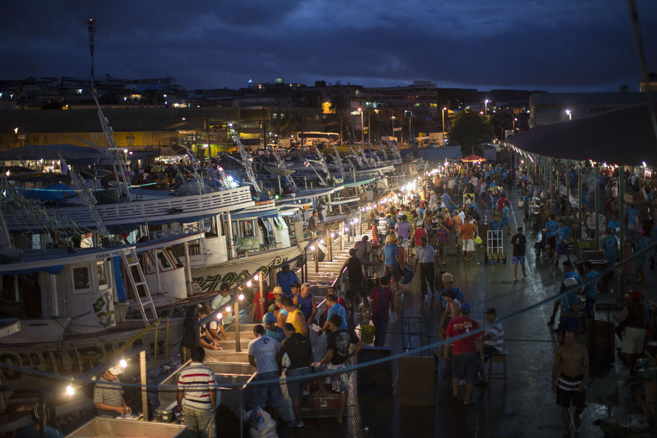 """Photo - In this May 24, 2014 photo, people buy fish as dawn begins to break at the Panair Fish Market in Manaus, Brazil. Eight teams are slated to play in the city - the U.S., England, Italy, Switzerland, Croatia, Cameroon, Portugal and Honduras - and they have their work cut out for them in dealing with the heat and humidity. """"There are two seasons in Manaus,"""" a local adage goes, """"summer and hell."""" (AP Photo/Felipe Dana)"""