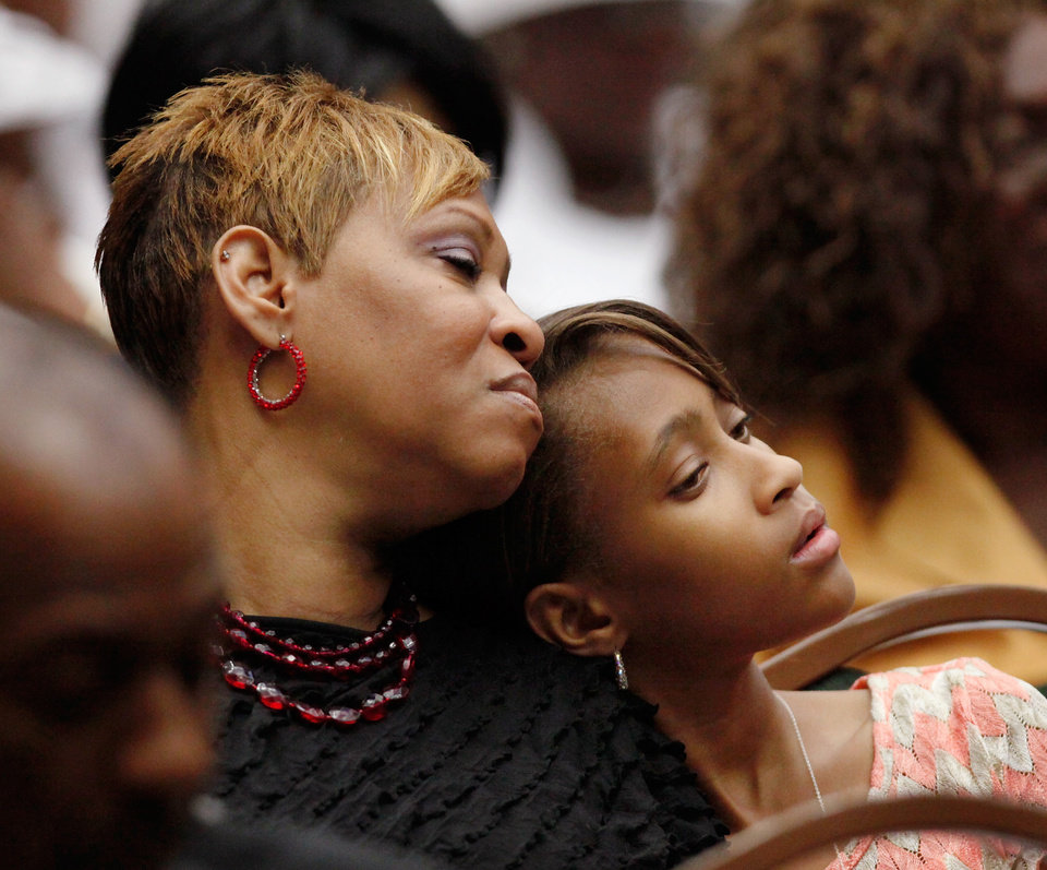 Photo - Maya Woodson, 12,  rests her head against the shoulder of her mother, Deidre Woodson. Deidre's husband, Harold Woodson was an honorary pallbearer. About 2,500 people celebrated the life and legacy of Oklahoma City civil rights pioneer Clara Mae Shepard Luper  during a lively service in the Cox Convention Center that lasted more than three hours, Friday,  June 17, 2011.  Luper died  last week at the age of 88. Photo by Jim Beckel, The Oklahoman