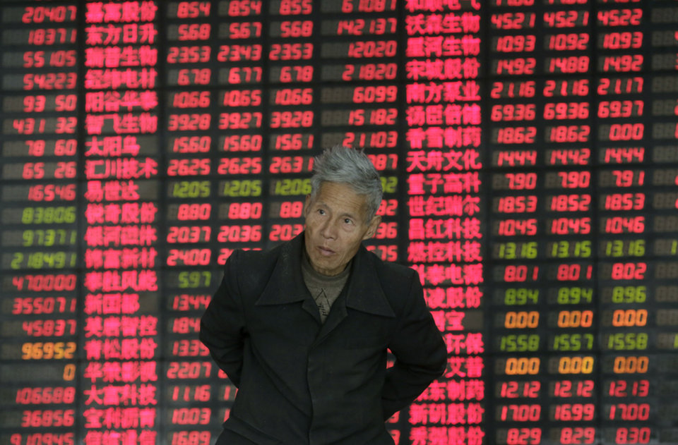 An investor walks in front of  the stock price monitor at a private securities company on Wednesday, March 6, 2013. The Dow's new all-time high and better economic data from the United States propelled Asian stock markets higher Wednesday. (AP Photo/Eugene Hoshiko)