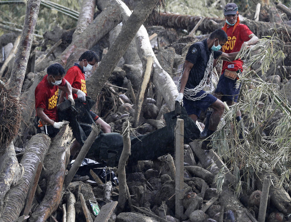Photo - Rescuers retrieve flash flood victims from the debris of Tuesday's Typhoon Bopha at New Bataan township, Compostela Valley in southern Philippines Friday Dec. 7, 2012. Rescuers were digging through mud and debris Friday to retrieve more bodies strewn across a farming valley in the southern Philippines by a powerful typhoon. (AP Photo/Bullit Marquez)