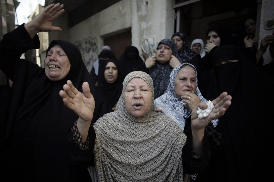 Photo - Palestinians grieve over the death of their relative Widad Mustafa Deif, 27, who was killed along with her 8-month-old son Ali Mohammed Deif in Israeli strikes in Gaza City late Tuesday, during their funeral in Jabaliya refugee camp in the northern Gaza Strip, Wednesday, Aug. 20, 2014. She was the wife of Mohammed Deif, the leader of the Hamas military wing. (AP Photo/Khalil Hamra)