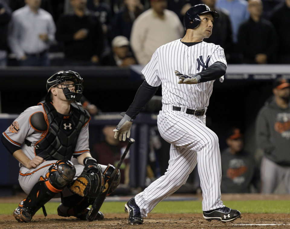 New York Yankees\' Raul Ibanez follows through on a home run as Baltimore Orioles catcher Matt Wieters watches during the ninth inning of Game 3 of the American League division baseball series Wednesday, Oct. 10, 2012, in New York. (AP Photo/Kathy Willens)