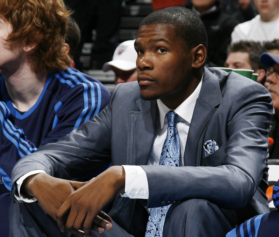 Photo - Oklahoma City's Kevin Durant watches the game from the bench in the first half during the NBA basketball game between the Dallas Mavericks and the Oklahoma City Thunder at the Ford Center in Oklahoma City, March 2, 2009. Durant did not play due to injury. BY NATE BILLINGS, THE OKLAHOMAN