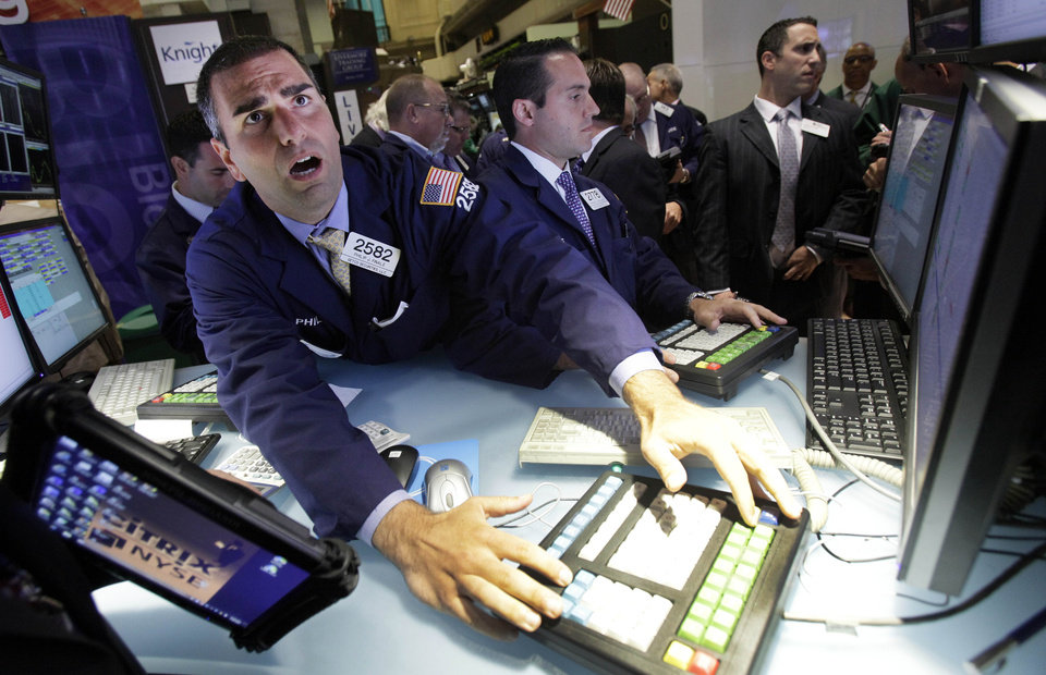 Photo -   Specialist Philip Finale, left, works at his post on the floor of the New York Stock Exchange Thursday, July 26, 2012. U.S. stocks soared at the opening bell after the president of the European Central Bank vowed to do what it takes to preserve the continent's monetary union. (AP Photo/Richard Drew)