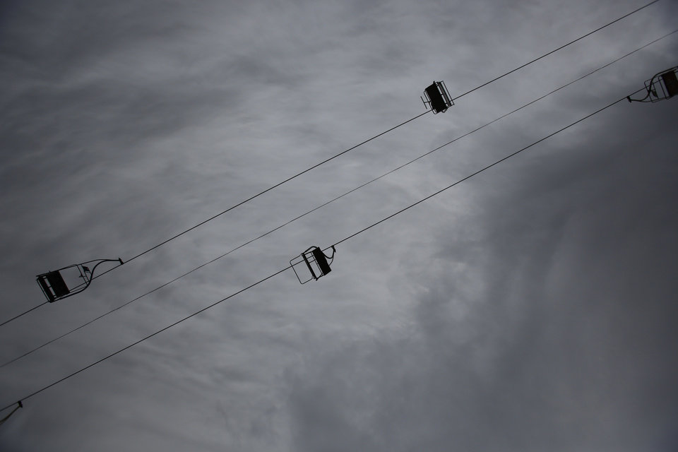 Photo - In this picture taken, Friday, Feb. 21, 2014, an empty chairlift is seen near the ski jumping facility at Mt. Igman near the Bosnian capital of Sarajevo. Wartime destruction and negligence have turned most of Sarajevo's 1984 Winter Olympic venues into painful reminders of the city's golden times. The world came together in the former Yugoslavia in 1984 after the West had boycotted the 1980 Olympics in Moscow and Russia boycotted the 1984 Summer Games in Los Angeles. Just eight years later, the bobsleigh and luge track on Mount Trbevic was turned into an artillery position from which Bosnian Serbs pounded the city for almost four years. Today, the abandoned concrete construction looks like a skeleton littered with graffiti. (AP Photo/Amel Emric)