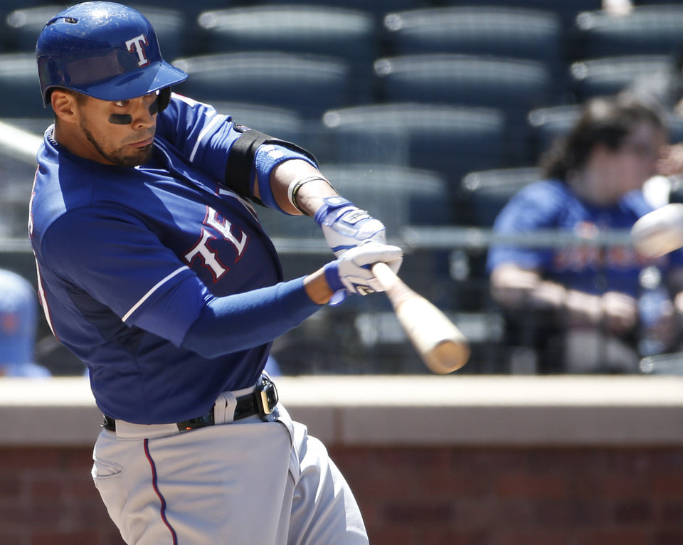 Photo - Texas Rangers Robinson Chirinos hits a fourth-inning solo home run off New York Mets starting pitcher Zack Wheeler in an interleague baseball game in New York, Sunday, July 6, 2014. (AP Photo/Kathy Willens)