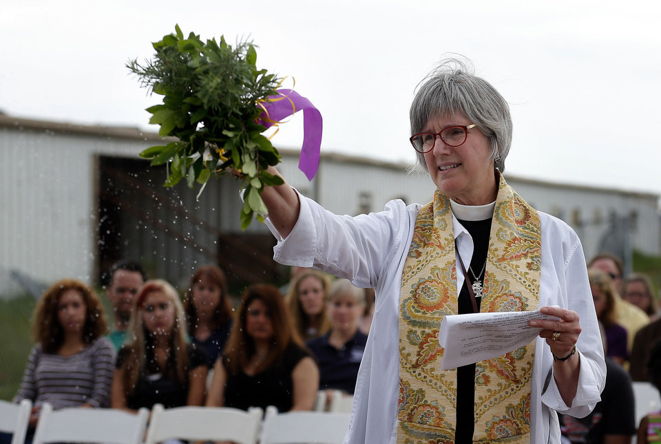 Photo - The Rev. Susan Joplin, a canon at St. Paul's Episcopal Cathedral, spreads holy water on a memorial flower garden during a memorial Saturday at the Orr Family Farm, 14400 S Western, to honor animals that died in the May tornadoes.   SARAH PHIPPS - SARAH PHIPPS