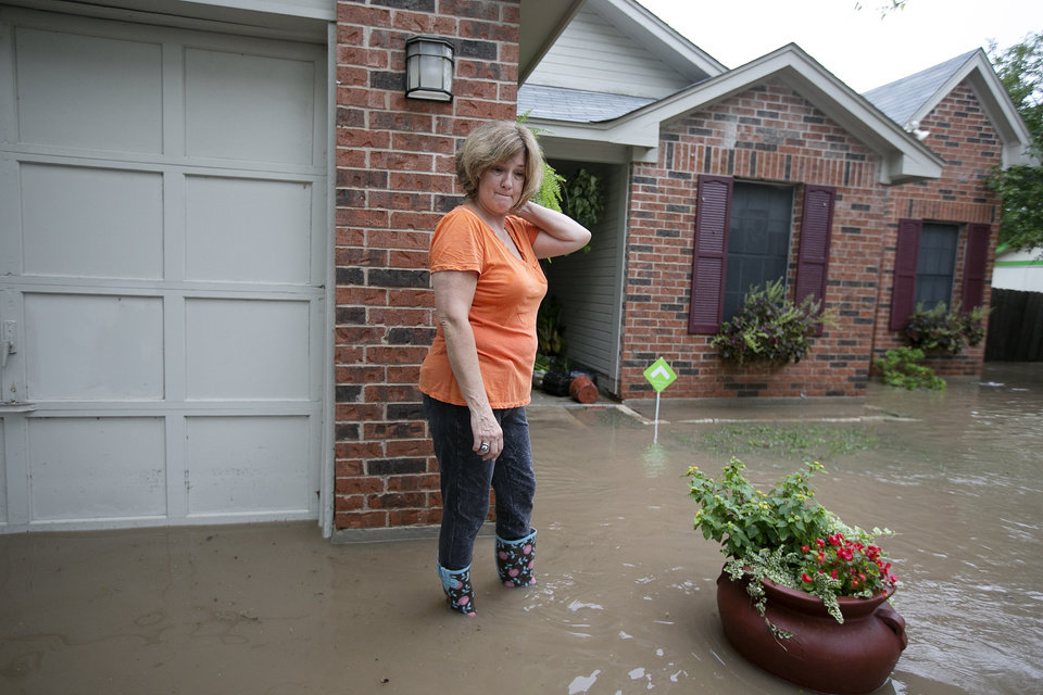 Photo - Barbara Smitherman stands in front of her flooded home in southeast Austin, Texas, on Thursday, Oct. 31, 2013. Heavy overnight rains brought flooding to the area. The National Weather Service said more than a foot of rain fell in Central Texas, including up to 14 inches in Wimberley, since rainstorms began Wednesday.  (AP Photo/The Austin American-Statesman, Deborah Cannon) AUSTIN CHRONICLE OUT, COMMUNITY IMPACT OUT, INTERNET MUST CREDIT PHOTOGRAPHER AND STATESMAN.COM, NO SALES