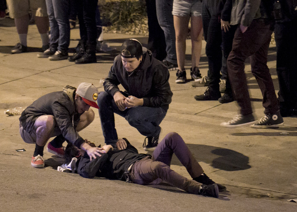 Photo - Bystanders tend to a man who was struck by a vehicle on Red River Street in downtown Austin, Texas, during SXSW on Wednesday March 12, 2014.  Police say two people were confirmed dead at the scene after a car drove through temporary barricades set up for the South By Southwest festival and struck a crowd of pedestrians.  (AP Photo/Austin American-Statesman, Jay Janner)