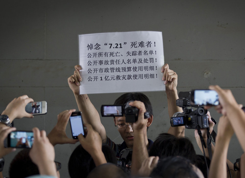 Photo -   Journalists and pedestrian film a man holding up a banner which reads