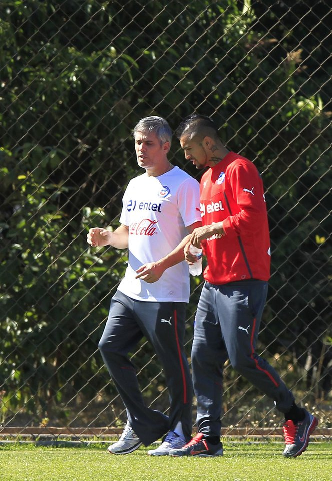 Photo - Chile's Arturo Vidal, right, walks with physical therapist Jose Amador, during a training session at Toca da Raposa 2, in Belo Horizonte, Brazil, Monday, June 9, 2014. Vidal, who is recovering from an injury, did not train. Chile will play in group B of the Brazil 2014 World Cup. (AP Photo/Bruno Magalhaes)