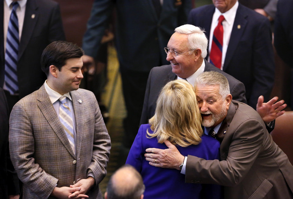 Photo - Gov. Mary Fallin is hugged by Sen. Larry Boggs as she makes her way out of the House chamber after delivering her speech. Fallin paused at lawmakers' desks to greet legislators as she left. At far left is Rep. Eric Proctor. Behind Fallin is Rep. Steve Kouplen.  The governor outlined her goals for the upcoming legislative session during her state of the state speech to a joint session of the legislature in the House chamber at the state Capitol on Monday, Feb. 3, 2014.   Photo by Jim Beckel, The Oklahoman