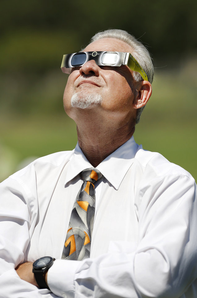 Photo - Dr. Jim McCharen, superintendent of Choctaw/Nicoma Park Public Schools, joins students at James Griffith Intermediate School to view the solar eclipse. The entire student body, faculty and some parents gathered in a field on the north side of JGI to view the solar eclipse Monday afternoon, Aug. 21, 2017.  Special glasses with very dark lenses were purchased to allow teachers and students to safely view the celestial event. Children were served  Moon Pies as a snack to enjoy while viewing the eclipse. Photo by Jim Beckel, The Oklahoman