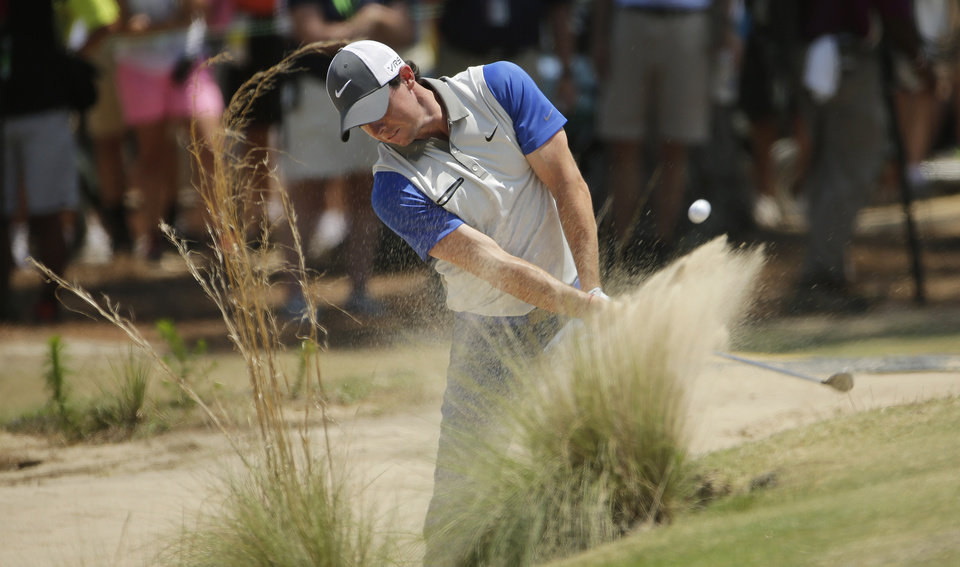 Photo - Rory McIlroy, of Northern Ireland, hits from the natural area on the third hole during the final round of the U.S. Open golf tournament in Pinehurst, N.C., Sunday, June 15, 2014. (AP Photo/Chuck Burton)