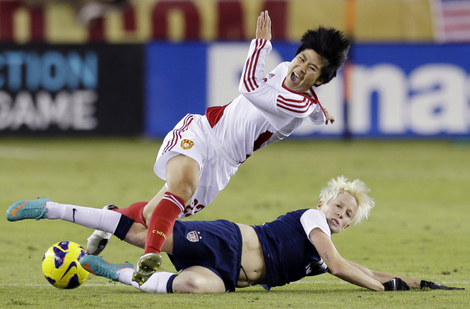 China's Ren Guixin and United States' Megan Rapinoe go after the ball during the second half of an exhibition soccer match, Wednesday, Dec. 12, 2012, in Houston. (AP Photo/David J. Phillip)