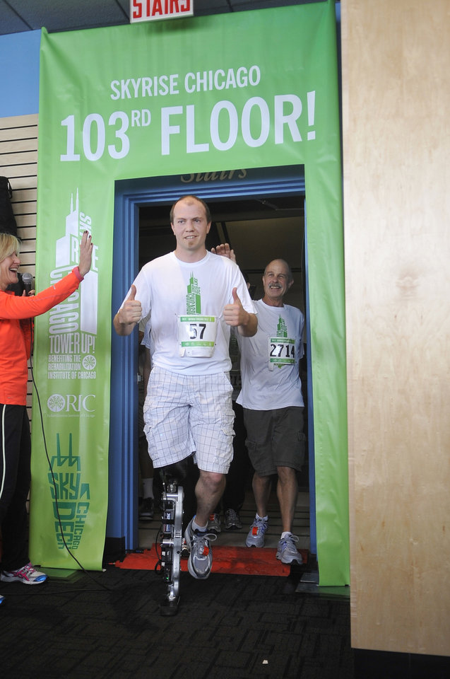 Photo -   Zac Vawter, a 31--year-old amputee, emerges after walking up the stairs of the Willis Tower in Chicago, Sunday, Nov. 4, 2012, to become the first person to climb the 103 floors of one of the world's tallest skyscrapers with a bionic leg. Vawter was wearing a prosthetic leg controlled by his mind while participating in