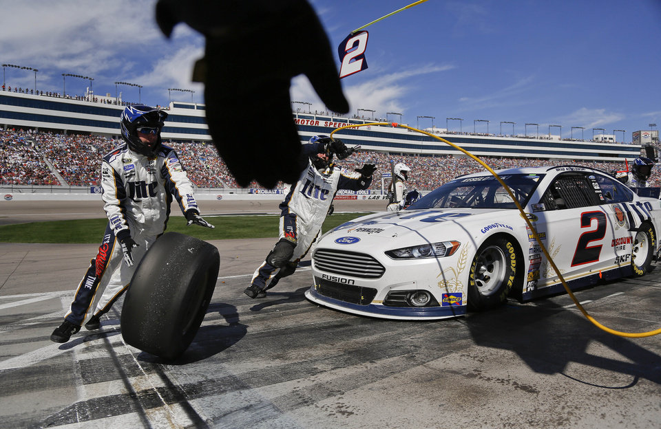Photo - A pit crew member reaches to grab one of the used tires off of Brad Keselowski's car during a pit stop at a NASCAR Sprint Cup Series auto race on Sunday, March 9, 2014, in Las Vegas. (AP Photo/Julie Jacobson)