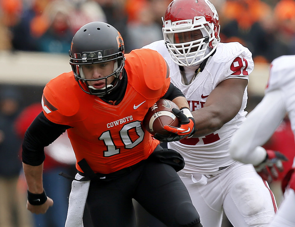 Oklahoma State's Clint Chelf (10) tries to get away from Oklahoma's Charles Tapper (91) during the Bedlam college football game between the Oklahoma State University Cowboys (OSU) and the University of Oklahoma Sooners (OU) at Boone Pickens Stadium in Stillwater, Okla., Saturday, Dec. 7, 2013. Oklahoma won 33-24. Photo by Bryan Terry, The Oklahoman