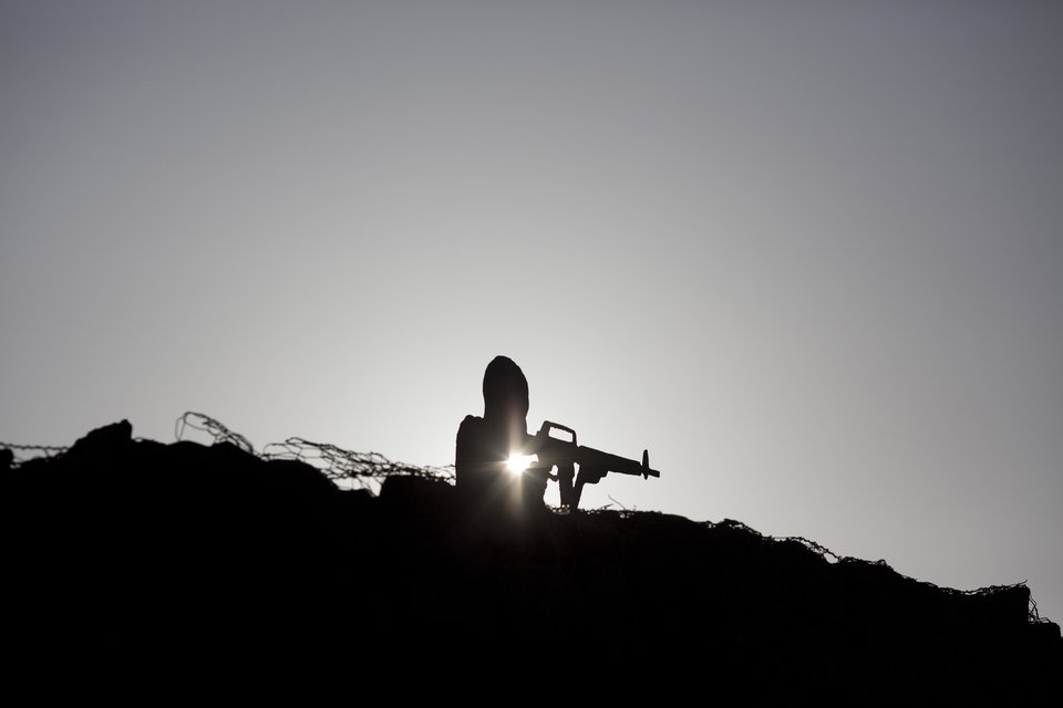 Photo - A metal board in the shape of a gunman sits on an old bunker at an observation point on Mt. Bental in the Israeli-controlled Golan Heights, overlooking the border with Syria Syria's Quneitra province, Thursday, Aug. 28, 2014. From the Israeli side of the de facto border, large clouds of smoke could be seen, as gunfire and explosions sounded in the distance. Israeli soldiers observed the fighting. (AP Photo/Ariel Schalit)