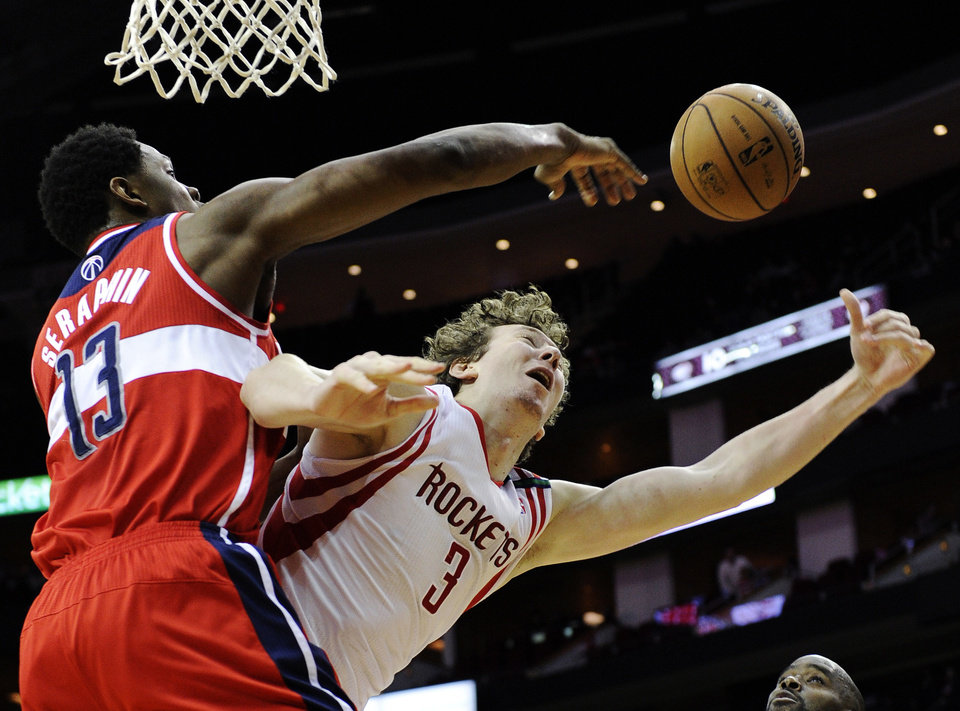 Houston Rockets\' Omer Asik (3) has the ball knocked away by Washington Wizards\' Kevin Seraphin (13) in the second half of an NBA basketball game, Wednesday, Dec. 12, 2012, in Houston. The Rockets won 99-93. (AP Photo/Pat Sullivan)