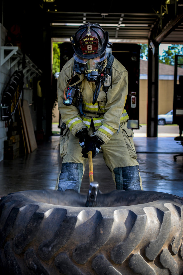 Photo -  Oklahoma City fire Maj. Brad Smith swings a sledgehammer during a morning workout and firefighter skills practice routine July 4 at Fire Station 8. [Photo by Cort Smith, for The Oklahoman]
