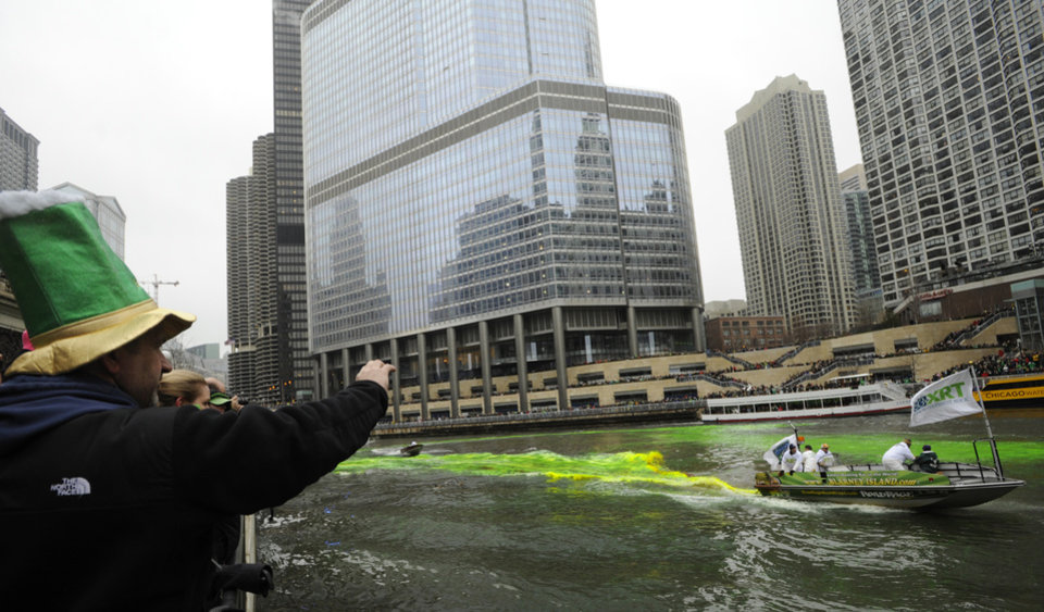 Photo - Bystanders look on as the Chicago River is dyed green ahead of the St. Patrick's Day parade in Chicago, Saturday, March, 16, 2013.  With the holiday itself falling on a Sunday, many celebrations were scheduled instead for Saturday because of religious observances. (AP Photo/Paul Beaty)