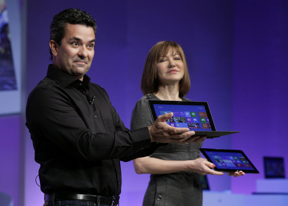 Mike Angiulo, corporate vice president of the Planning and PC Ecosystem team at Microsoft, shows the company's Surface tablet computer Thursday at the launch of Microsoft Windows 8 in New York. He is accompanied by Microsoft Vice President Julie Larson-Green. AP Photo