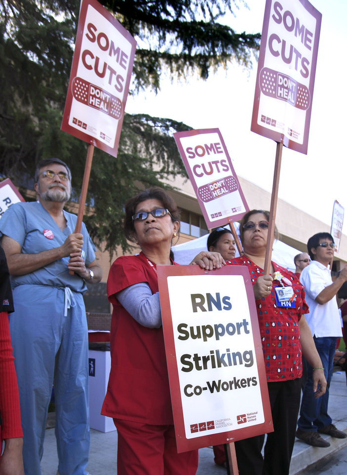 FILE -- In this Sept. 21, 2011 file photo, Kaiser Medical assistants Darlene De LaTorra, left, Latisha Tucker, Registered Nurse Edith Fernandez, center, joins more than 200 other health care workers and their supporters in a demonstration outside the Kaiser in Sacramento, Calif. If approved by voters in November, Proposition 32 would prohibit corporations and unions, like the California Nurses Association, from collecting money for state political activities from employees or members through paycheck deductions. It also prohibits unions and corporations from making donations to state candidates.(AP Photo/Rich Pedroncelli,File)