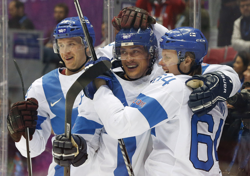 Photo - Finland forward Teemu Selanne, center, celebrates with teammates forward Lauri Korpikoski, left, and forward Mikael Grandlund after scoring a goal against the USA during the second period of the men's bronze medal ice hockey game at the 2014 Winter Olympics, Saturday, Feb. 22, 2014, in Sochi, Russia. (AP Photo/Mark Humphrey)