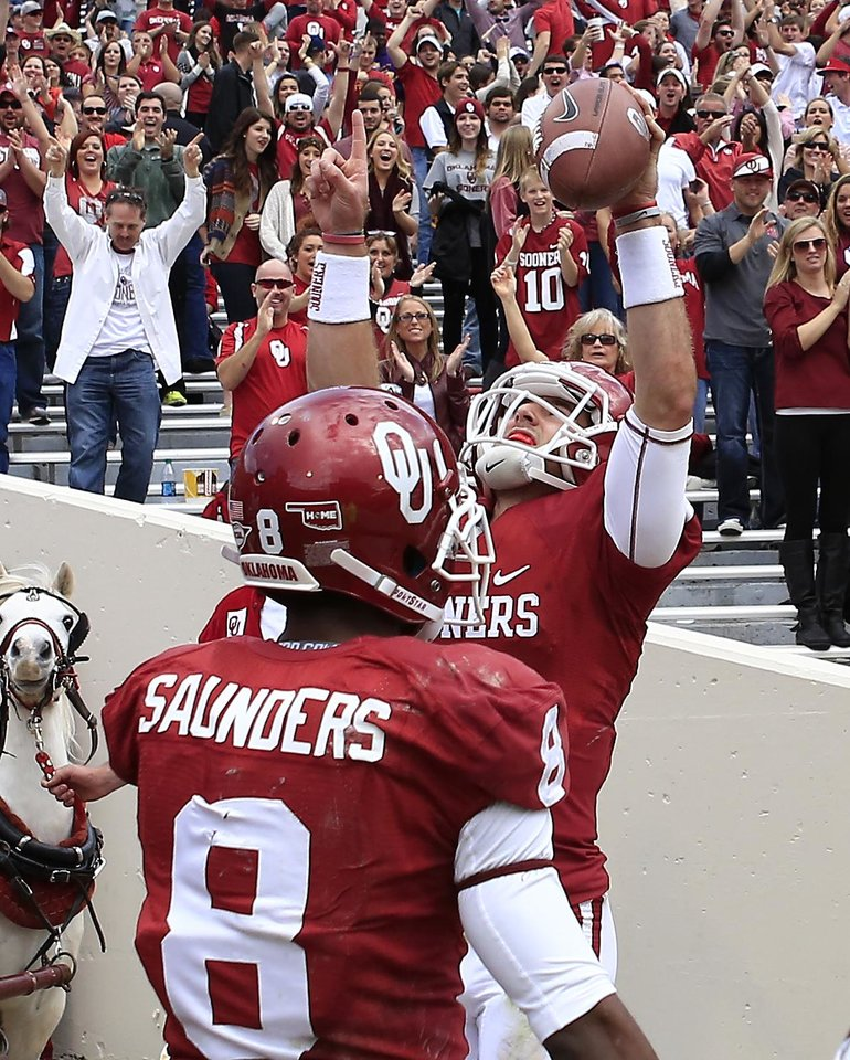 Photo - Oklahoma Trevor Knight and Jalen Saunders celebrate after Knight's touchdown against Iowa State in the third quarter of an NCAA college football game in Norman, Okla. on Saturday, Nov. 16, 2013. Oklahoma won 48-10.  (AP Photo/Alonzo Adams)