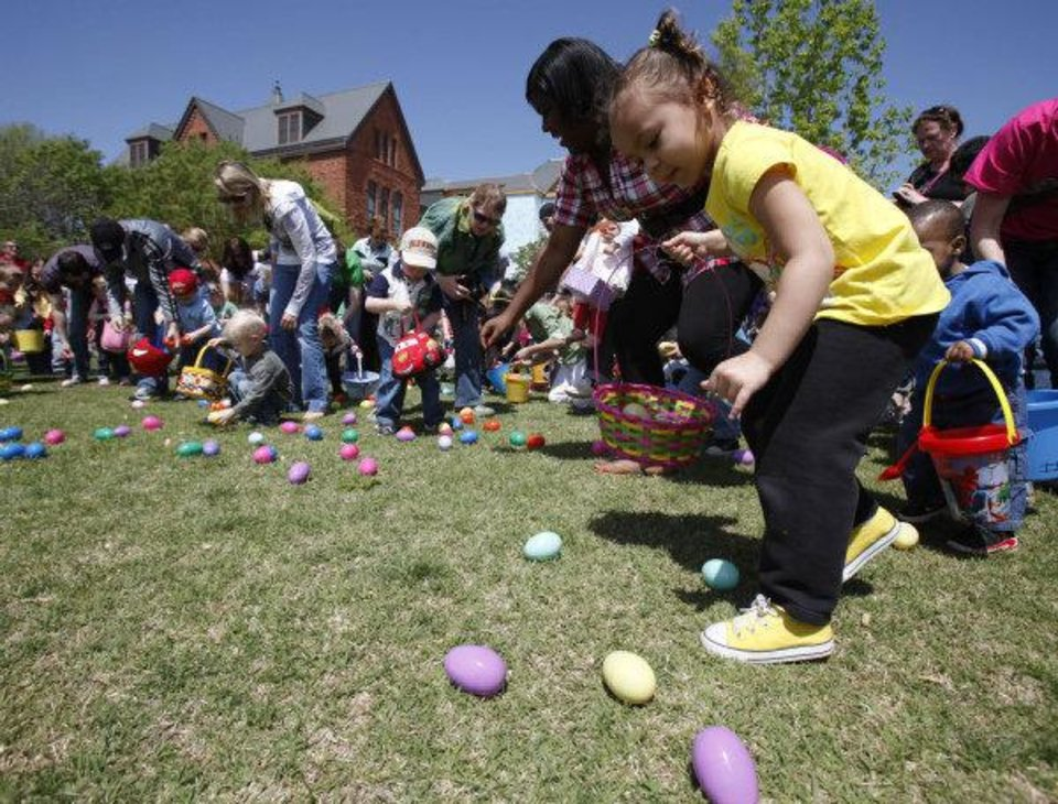 Photo - Children rush the field to pick up Easter eggs Saturday during an Easter egg hunt and carnival at Plunkett Park at the University of Central Oklahoma in Edmond. Photo by Paul Hellstern, The Oklahoman  PAUL HELLSTERN