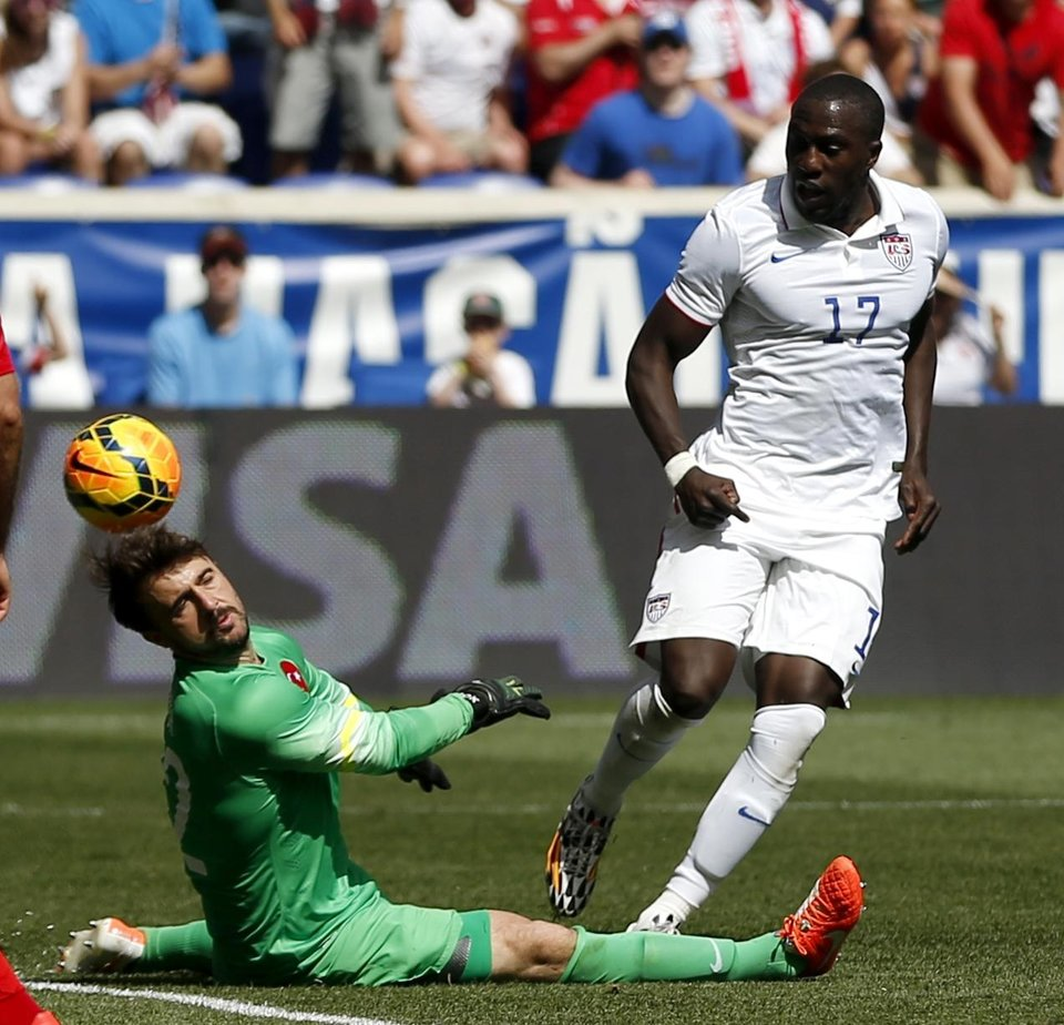 Photo - Turkey goalkeeper Onur Recep Kivrak, left, deflects a shot by United States' Jozy Altidore in the second half of an international soccer friendly, Sunday, June 1, 2014, in Harrison, N.J. The U.S. won 2-1. (AP Photo/Julio Cortez)