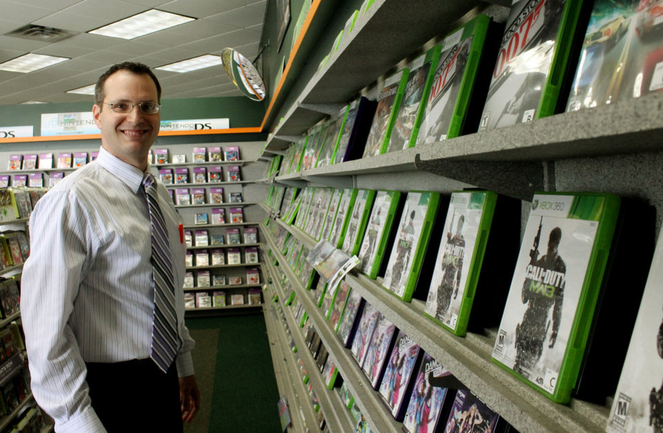 Photo - Store Manager Heath Clark, 34, stands by game rentals at a Family Video store on N Western Avenue in Edmond on March 21.  Tiffany Gibson - THE OKLAHOMAN
