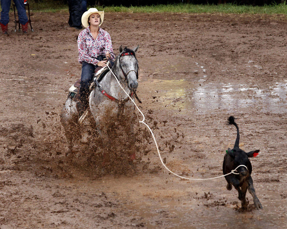Photo - Kassi McPherson, Rapid City, SD, compete in a muddy Breakaway Roping at the International Youth Finals Rodeo in Shawnee at the Heart of Oklahoma Exposition Center, Wednesday, July 9, 2014. Photo by David McDaniel, The Oklahoman