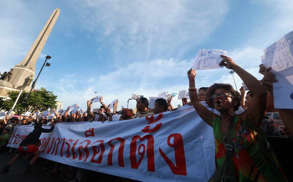 Photo - Protesters hold banners and chant slogans during an anti-coup demonstration at the Victory Monument in Bangkok, Thailand, Saturday, May 24, 2014. Thailand's coup leaders said Saturday that they would keep former Prime Minister Yingluck Shinawatra, Cabinet members and anti-government protest leaders detained for up to a week to give them