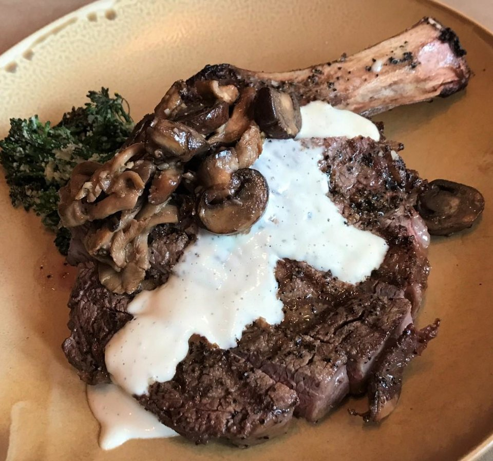 Photo - Bone-in ribeye with wild mushrooms and agliata sauce from Patrono in downtown Oklahoma City. [Dave Cathey/The Oklahoman]