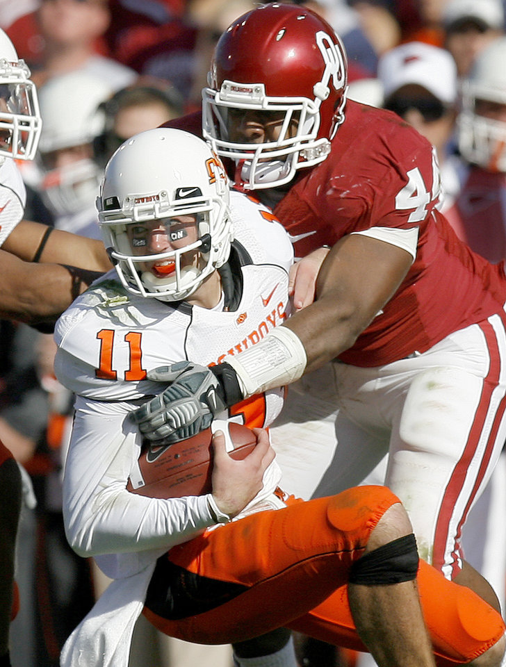 Photo - OSU's Zac Robinson is brought down by OU's Jeremy Beal during the first half of the Bedlam college football game between the University of Oklahoma Sooners (OU) and the Oklahoma State University Cowboys (OSU) at the Gaylord Family-Oklahoma Memorial Stadium on Saturday, Nov. 28, 2009, in Norman, Okla.