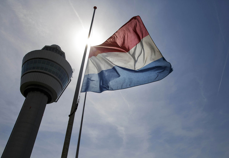Photo - A flag flies half-staff near the traffic tower at Schiphol airport in Amsterdam, Friday, July 18, 2014. The attack on a Malaysian jetliner Thursday afternoon killed 298 people from nearly a dozen nations, more than half being Dutch, including vacationers, students and a large contingent of scientists heading to an AIDS conference in Australia. (AP Photo/Phil Nijhuis)