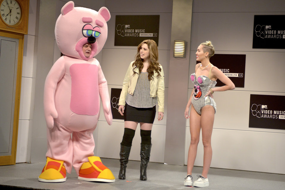 Photo - This Oct. 5, 2013 photo released by NBC shows, from left,  Bobby Moynihan, Vanessa Bayer and guest host Miley Cyrus in a scene from the late-night comedy series
