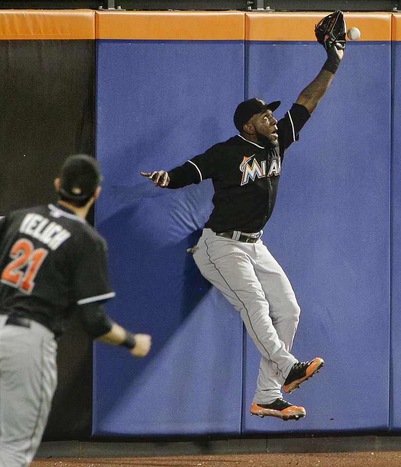 Photo - Miami Marlins center fielder Marcell Ozuna just misses making a catch at the wall on a ball hit by New York Mets' Kirk Nieuwenhuis for a triple in the sixth inning of a baseball game, Friday, July 11, 2014, in New York. (AP Photo/Julie Jacobson)