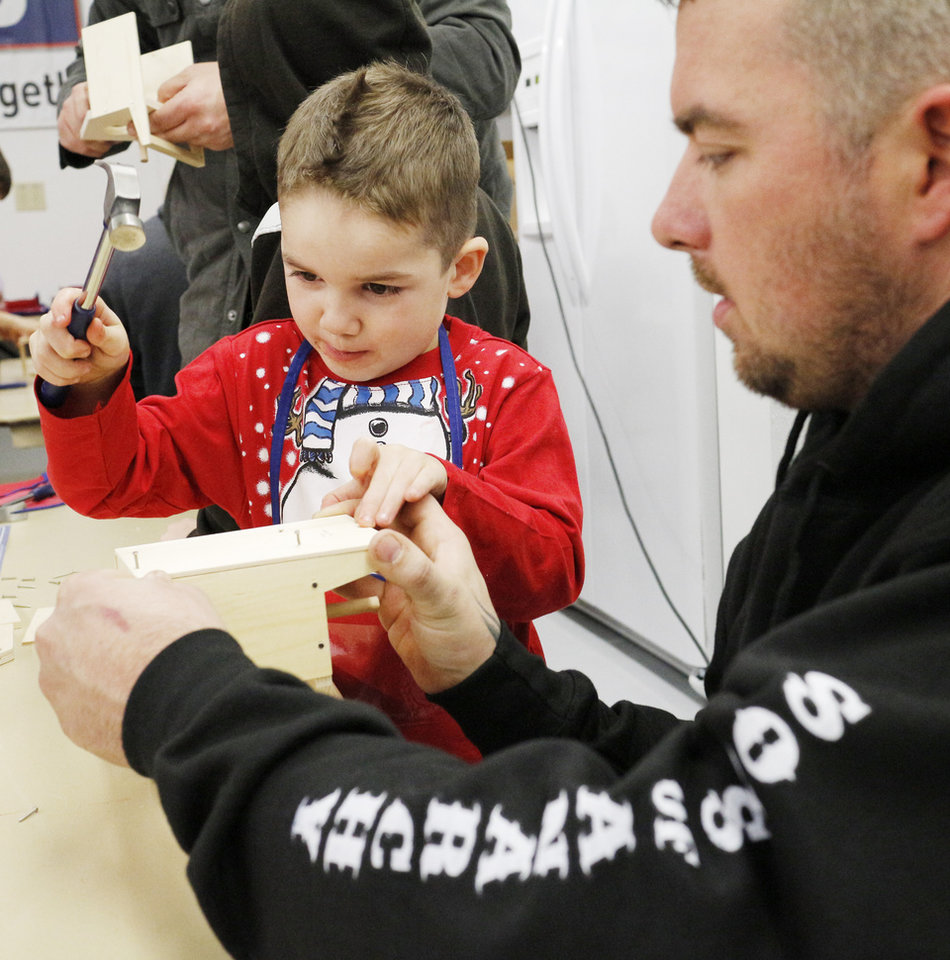 Photo -  Greg Carter helps his son, Chance Carter, 4, build a birdhouse in Santa's workshop during Edmond Fire Department's annual Winter Night. PHOTO BY DOUG HOKE, THE OKLAHOMAN   DOUG HOKE -