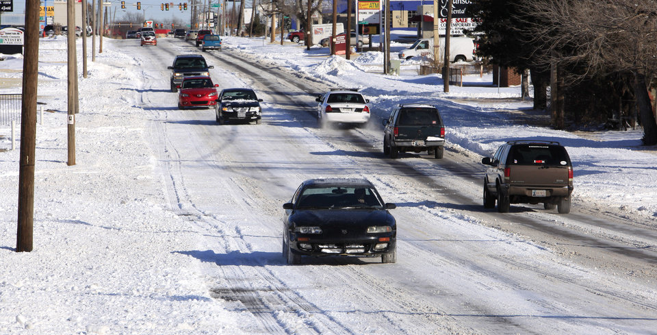 Photo - Cars try to negotiate a hill in the snow and ice on May Avenue at NW 69 Street in Oklahoma City Thursday, Feb. 3, 2011. Photo by Paul B. Southerland, The Oklahoman